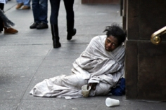 A panhandler begs for money on Fifth Avenue in New York